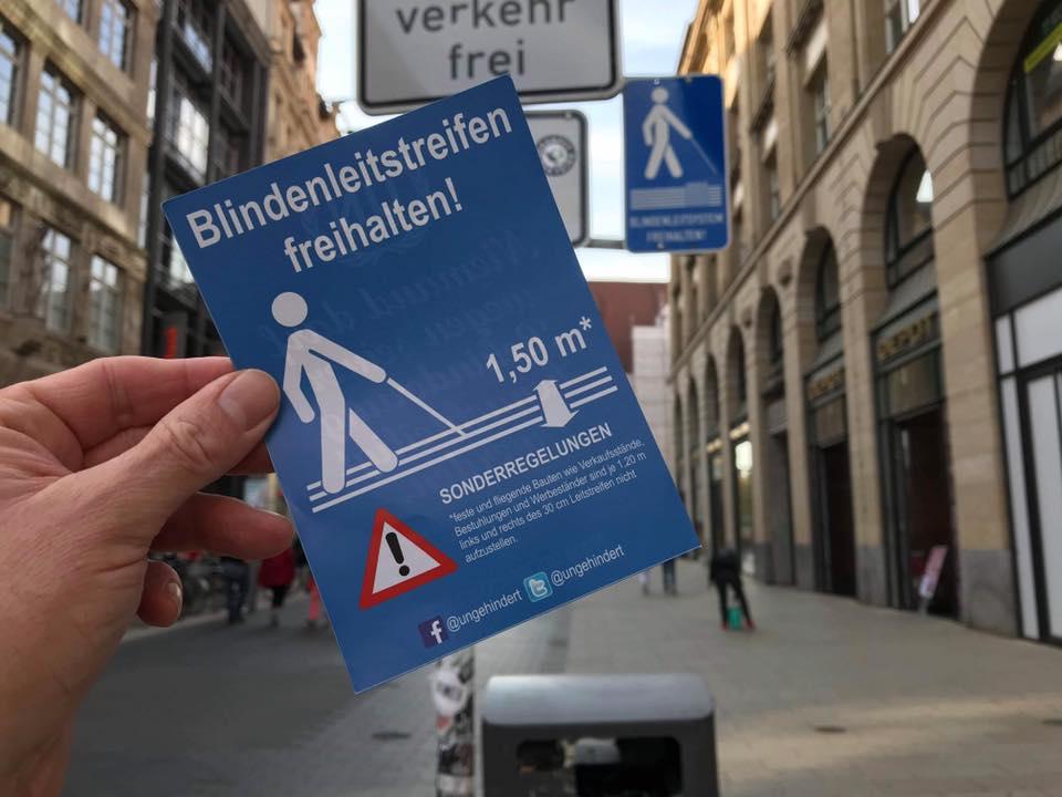 ©-Foto- Im Vordergrund eine Hand mit dem Aktionszettel. Im Hintergrund das Hinweisschild zum Leitsystem.